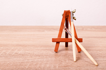 ravage: A close up shot of paint brushes and an easel on a wooden table. Stock Photo