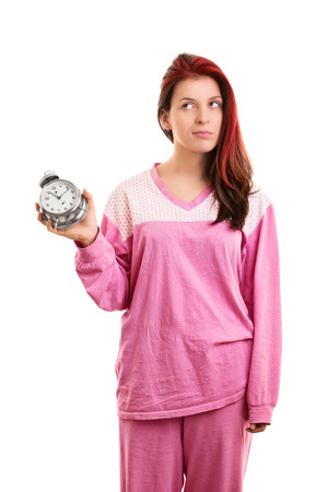 morning routine: A portrait of a young girl in pyjamas holding an alarm clock, isolated on white background.