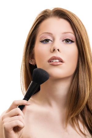 A portrait of a beautiful woman applying makeup, isolated on white background.