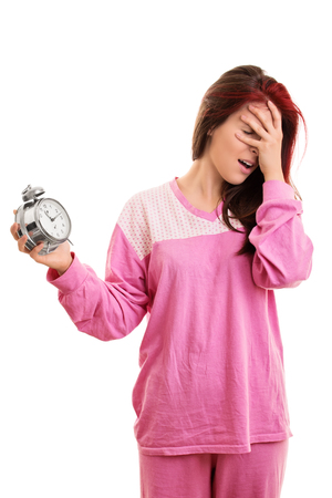Portrait of a young girl, holding an alarm clock, panicking because she overslept, isolated on white background.