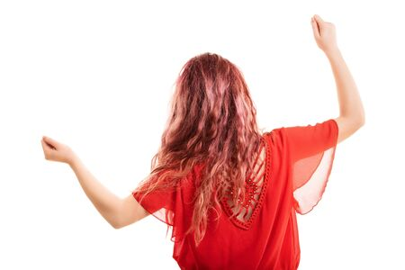 Redheaded girl turned with her back, dancing, gesturing with arms up, isolated on a white background Archivio Fotografico