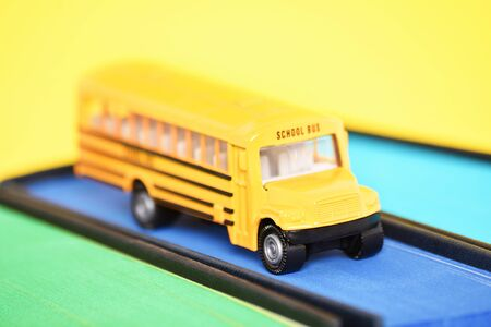 Close up shot of a toy school bus on top of a book with blue sprayed edges on yellow background.