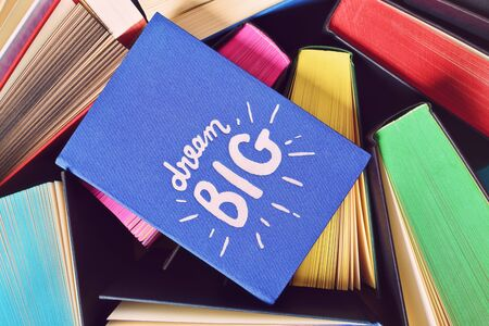 Close up shot of a blue notebook with inspirational dream big sign, on top of open books with multicolored sprayed edges.