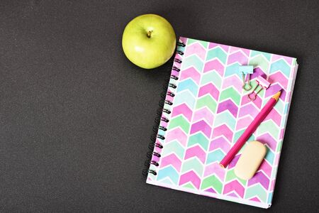 Top view of girly pink notebook with pencil, eraser, binder clips and apple on black background. Stok Fotoğraf