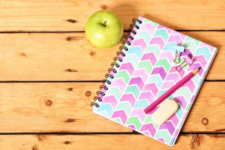 Top view of girly pink notebook with pencil, eraser, binder clips and apple on wooden background.