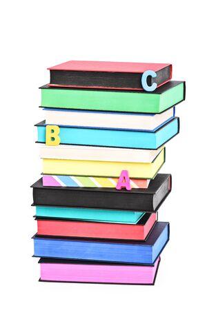 Stapel von bunten Büchern mit verschiedenen gesprühten Kanten und verstreuten Buchstaben, die ABC buchstabieren, isoliert auf weißem Hintergrund.