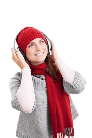 Beautiful smiling girl with red scarf and hat in winter clothes, listening to music on her headphones, isolated on white background.