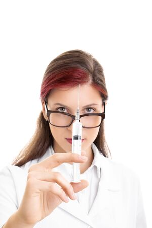 Close up shot of a young female doctor with glasses holding a syringe with needle, isolated on white background. Imagens - 131942838