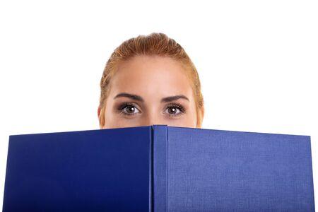 Toma de primer plano de una niña que cubre la mitad de su rostro con un libro, aislado sobre fondo blanco.