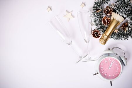 Christmas or New Year composition. Champagne bottle with two glasses, decoration and a clock showing almost midnight, on white background. Christmas, New Year concept. Flat lay,  top view.