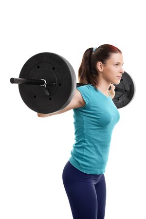Beautiful fit young girl with barbell on her shoulders getting ready to do squats, isolated on white background.