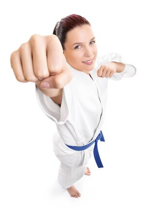 Top down portrait of a beautiful young female fighter in white kimono attacking isolated on white background. Girl in white kimono with blue belt.