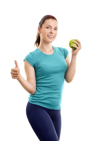Healthy, lifestyle, diet, weight loss concept. Portrait of a confident, sporty, smiling beautiful young woman in sports clothes, holding a green apple and giving thumb up, isolated on white background. 版權商用圖片