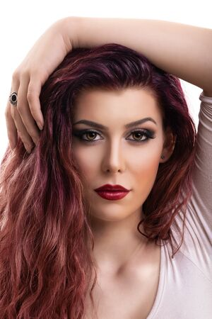 Close up profile shot of a beautiful redhead young woman with dark smokey eye makeup and red lipstick, isolated on white background. Female fashion. Beautiful young woman with perfect skin and long hair. Imagens