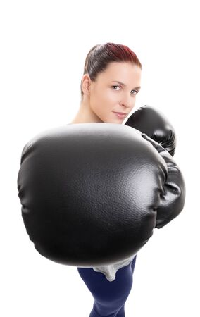 Primer plano de una joven y bella mujer con guantes de boxeo puñetazos o pinchazos hacia la cámara, aislado sobre fondo blanco. Concéntrese en el guante de boxeo negro. Concepto de deporte.