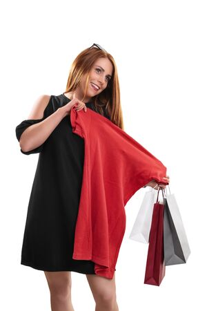 Shopping concept. Beautiful smiling woman happy with her shopping, holding shopping bags and a new red dress or blouse, isolated on white background.