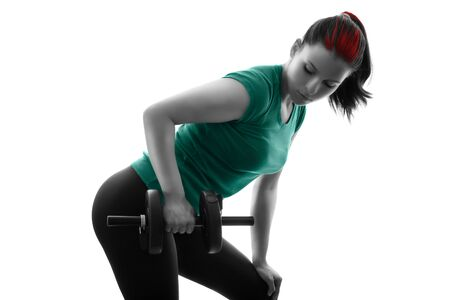 Fit attractive young woman working out with a set of dumbbells, doing bent-over row, backlit silhouette studio shot isolated on white background. Fitness and healthy lifestyle concept. Stock Photo
