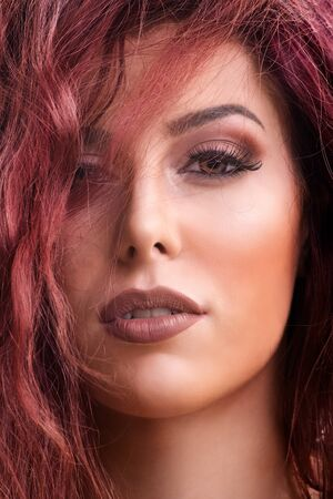 Close up portrait shot of a beautiful redhead young woman with dark smokey eye makeup and red lipstick with hair over her eye. Female fashion. Beautiful young woman with perfect skin and long hair. Imagens
