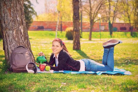 Beautiful smiling young girl lying on the green grass in the park, inserting a coin in a green piggy bank. Savings and money concept. Student saving concept. Stock Photo