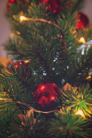 Close up of a Christmas tree with decoration. Red ornament on a Christmas tree with bokeh. Christmas, winter, new year concept.