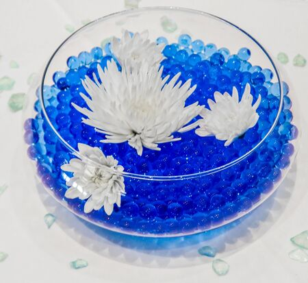 white flowers in blue glass bead fish bowl