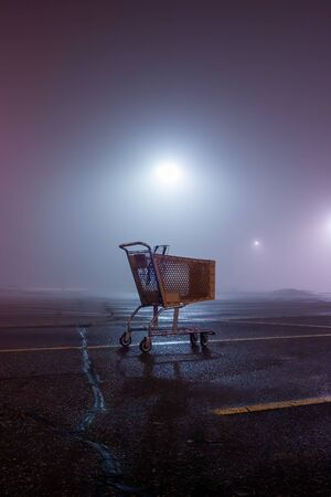 A foggy evening with a lone shopping cart in the parking lot