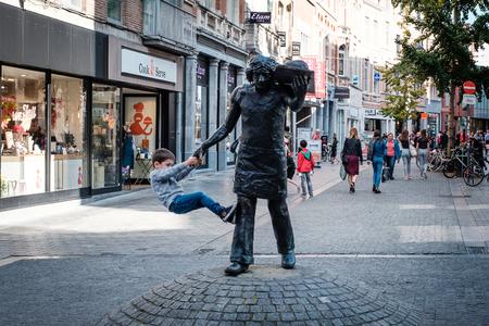 Leuven, België - 14 oktober 2017: Jonge jongen opknoping op een standbeeld in de stad Leuven Redactioneel