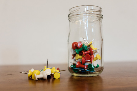 A small glass jar with drawing pins or pushpins on a desk