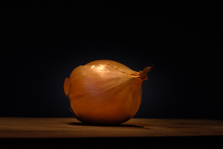 One onion on a cutting board, isolated from a black background Banco de Imagens