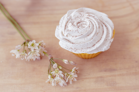 vanilla cupcake: Vanilla cupcake with white frosting and flowers on a table Stock Photo