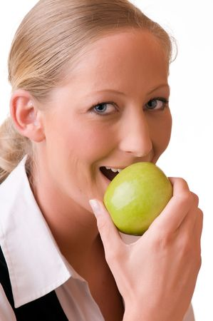 A young and pretty woman with perfect teeth is eating a green apple photo