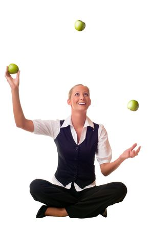 juggling: A blond and young woman is sitting on the floor and juggling a green apple
