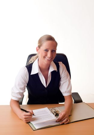A young and pretty businesswoman is working with a folder at the desk and smiles photo