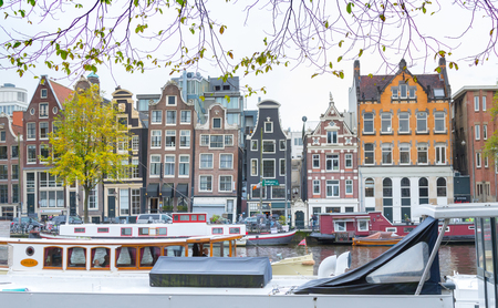 Traditional old buildings and boats at Amsterdam in autumn, Netherlands