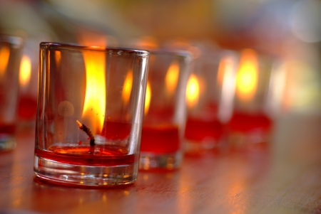Flame of a candle shines bright in the glass  Stock Photo