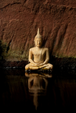 solemn: Buddha sat on a small river  There is a sandstone backdrop of solemn peace