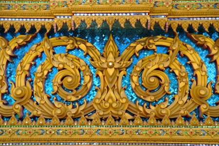 thai motifs: The golden flower Thai motif, decorated with blue reflective glass shows the delicate beauty of flowers  Thai motifs are part of the traditional Thai culture, and are often used to decorate the walls of Thai temples   Stock Photo