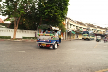 TukTuk servicing passenger at Khaosarn road Editorial