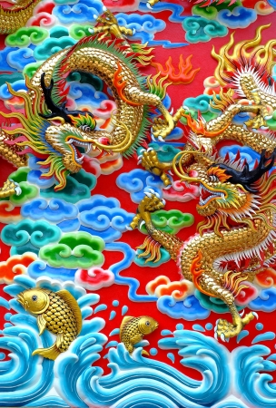 The carvings of the golden dragons and koi are displayed outside the walls of Kratuemsueapla Temple in Bangkok, Thailand  The carvings depict a Chinese myth where koi that are strong and brave enough to succeed in climbing the falls at the Dragon�s Gate   photo
