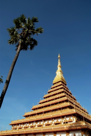 Nine-storey stupa of gold with Palm Tree in blue sky photo