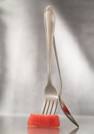 Fork,spoon and watermelon on gray background photo