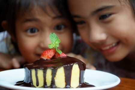 Two girls watch a cake and ready to eat