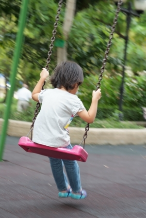 A girl playing swing in the park Stock Photo