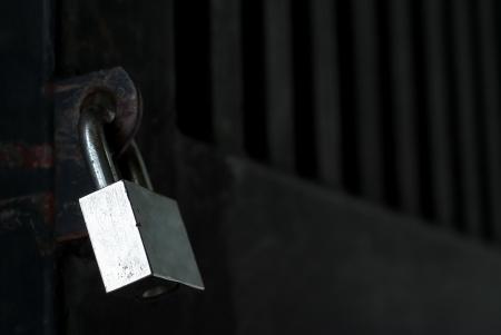 A silver metal lock on black door