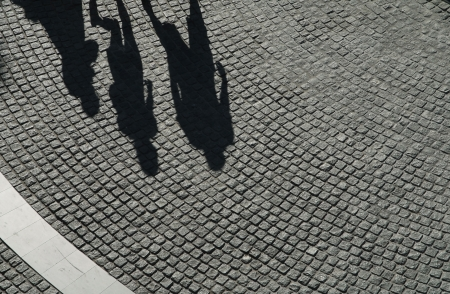 The three shadow of person on  black cobblestone photo