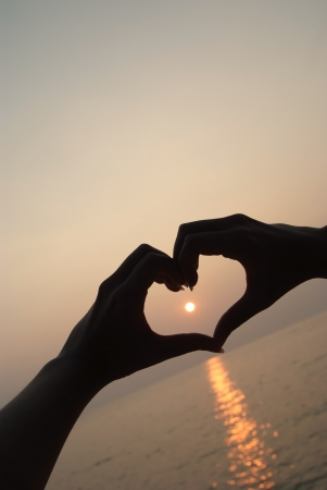 Heart symbol by hand on the beach with sunset