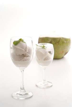 Coconut milk icecream in glasses with coconut on white background
