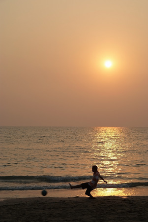 A boy playing football on the beach with sunset photo