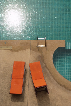 A swimming pool with couch on a top view