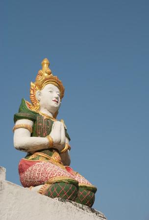 Thai fairy sculpture sit on the pagoda below a blue sky